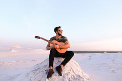 Attractive Arabian guy sings songs on guitar, sitting on hill in Stock Photography