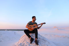 Attractive Arabian guy sings songs on guitar, sitting on hill in Stock Photos
