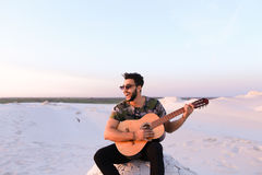 Attractive Arabian guy sings songs on guitar, sitting on hill in Stock Photo