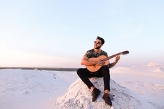 Attractive Arabian guy sings songs on guitar, sitting on hill in Stock Image