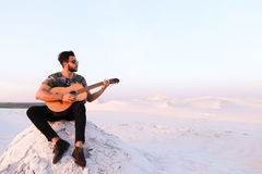 Attractive Arabian guy sings songs on guitar, sitting on hill in Stock Images
