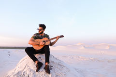 Attractive Arabian guy sings songs on guitar, sitting on hill in Royalty Free Stock Photography