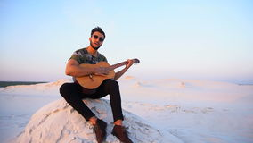 Attractive Arabian guy sings songs on guitar, sitting on hill in desert at sunset in open air in evening. Bearded Muslim young man enthusiastically plays guitar stock footage