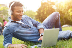 Attractive Arabian student is relaxing on lawn. Cheerful young men is using a laptop and smiling. He is lying on grass in park. The guy is listening to music Royalty Free Stock Images