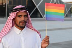 Attractive Arabic gay man holding the rainbow flag