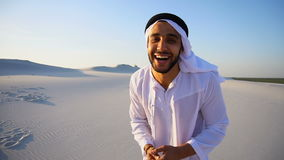 Attractive Arabic male guide talks about pros of traveling and looks at camera, standing in middle of wide desert in. Talkative handsome Muslim Arabian Sheikh stock footage
