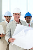 Attractive architect holding blueprints. And smiling at the camera Royalty Free Stock Photography