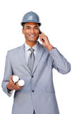 Attractive architect wearing a hardhat on phone royalty free stock photography