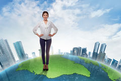 Attractive asian business woman standing on big earth with skysc. Rapers against blue sky background Stock Photography