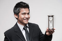 Attractive Asian Businessman holding a hour glass Stock Images