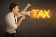 Attractive asian businessman holding megaphone with TAX announce. Ment over black wall background Royalty Free Stock Images