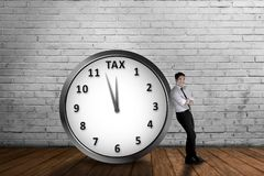 Attractive asian businessman lean back on the clock with tax dea. Dline. Goods and Services Tax concept Stock Image