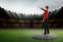 Attractive asian businessman standing and pointing to the sky. On podium royalty free stock images