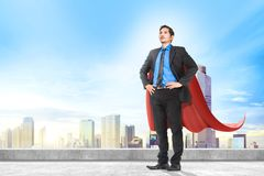 Attractive asian businessman with superhero cape standing on the rooftop of building. In the city royalty free stock image