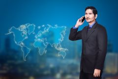 Attractive asian businessman talking on mobile phone. With modern background Stock Image