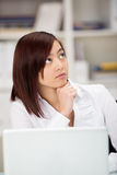 Attractive Asian businesswoman lost in thought Stock Photo