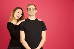 Attractive asian and caucasian inter racial hugging in studio sh. Ot against pink background Stock Photos