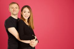 Attractive asian and caucasian inter racial hugging in studio sh. Ot against pink background royalty free stock photos