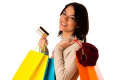 Attractive asian caucasian woman with shopping bags and credit card. In her hands isolated over white background Stock Image