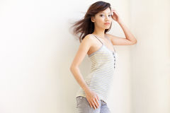 Attractive Asian Chinese Girl with windswept hair. Attractive Asian Chinese girl dressed casually in jeans and striped top posing with windswept hair shot Royalty Free Stock Photo