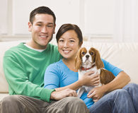 Attractive Asian Couple Holding Dog Stock Photos