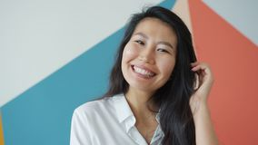 Attractive Asian female adult smiling laughing at home on colorful background