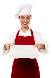Attractive asian female chef delivering pizza. Attractive young female chef delivering pizza to the customer Royalty Free Stock Image