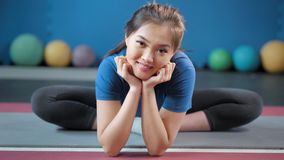 Attractive Asian female showing perfect stretching bending legs having good time ay gymnastic class. Full shot portrait of smiling flexible yoga woman sitting on stock video