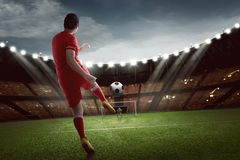 Attractive asian football player shooting the ball to goal. At match royalty free stock photography