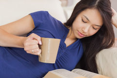 Attractive asian girl lying on the sofa reading a novel and drin Stock Photos