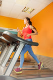 Attractive Asian girl running on the treadmill Royalty Free Stock Photography