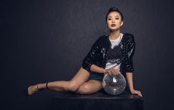 Attractive asian girl sitting and posing with disco ball Stock Photography