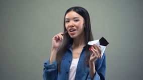 Attractive asian girl smiling on camera eating dark chocolate, advertisement. Stock footage stock video footage