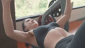 Attractive Asian girl in sportswear lying on gym bench and lifting up barbell at the fitness sport gym training center. Healthy. And Sport workout people stock video