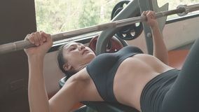 Attractive Asian girl in sportswear lying on gym bench and lifting up barbell at the fitness sport gym training center. Healthy. And Sport workout people stock footage