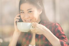 Attractive asian girl using smartphone and drinking coffee in cafe coffee. Break concept royalty free stock images
