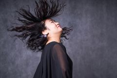 Attractive asian joyful happy female model is shaking head with brunette hair in studio wearing black dress, on royalty free stock images