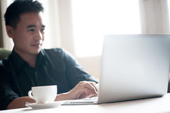 Attractive Asian Male using laptop. In the cafe Royalty Free Stock Image