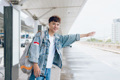 Attractive asian man stopping taxi at the airport Royalty Free Stock Image