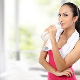Attractive asian smiling woman drinking water Royalty Free Stock Images