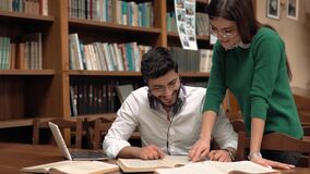 Girl Helps the Mate. Attractive asian student doing home assignment with laptop and books, wearing big headphones around the neck, pretty, slender girl comes and stock video footage