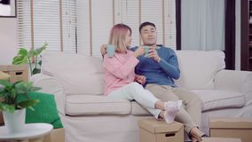 Attractive Asian sweet couple enjoy love moment drinking warm cup of coffee or tea in their hands on sofa in the living room. stock video footage