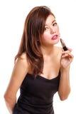 Attractive Asian woman applying lipstick Stock Image