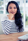 Attractive Asian woman with fist on chin posing for the camera Royalty Free Stock Photography
