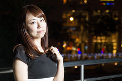 Attractive Asian Woman in front of Mall with bright LIghts. Portrait of an attractive Japanese tourist woman smiling and visiting a shopping mall in the city of Stock Photography