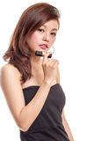 Attractive Asian woman holding lipstick royalty free stock photography