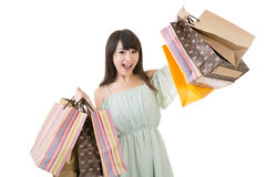 Attractive asian woman holding shopping bags. With exciting face. Portrait isolated on the white background Stock Photos