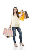 Attractive asian woman holding shopping bags. Full length portrait. Isolated on the white background Royalty Free Stock Photo
