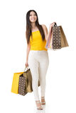 Attractive asian woman holding shopping bags. And posing in studio. Full length portrait. Isolated on the white background Royalty Free Stock Photos