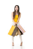 Attractive asian woman holding shopping bags. And posing in studio. Full length portrait. Isolated on the white background Royalty Free Stock Images